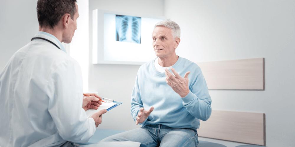older man talking with chiropractor