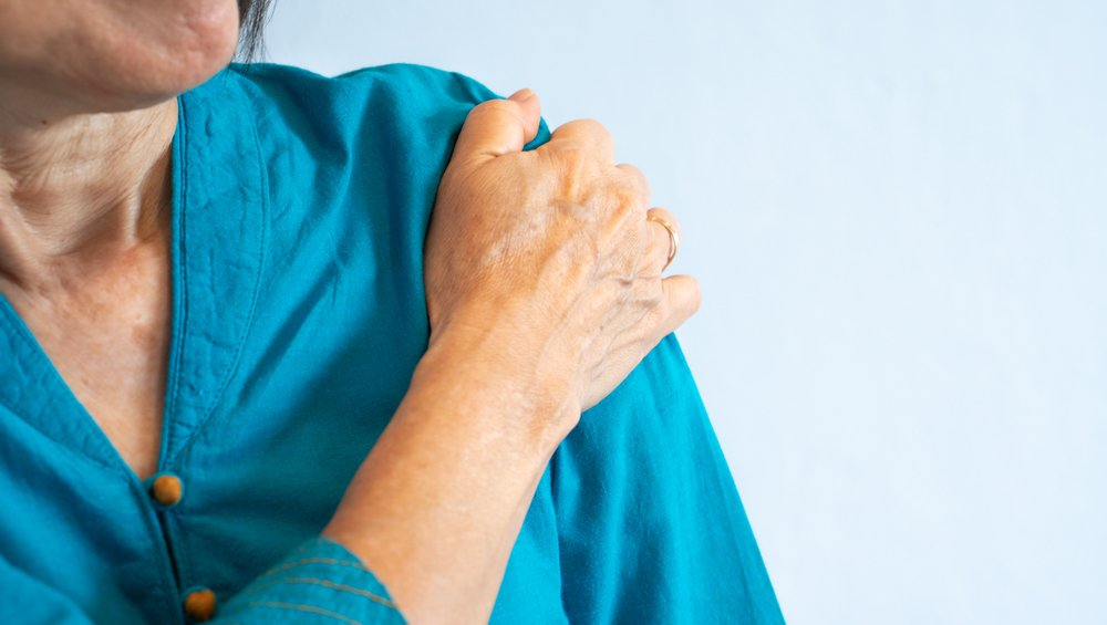 woman in blue shirt holding shoulder in pain