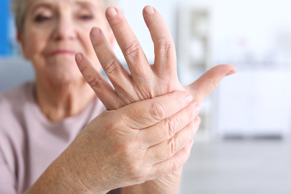 elderly woman gripping her hand to relieve arthritis