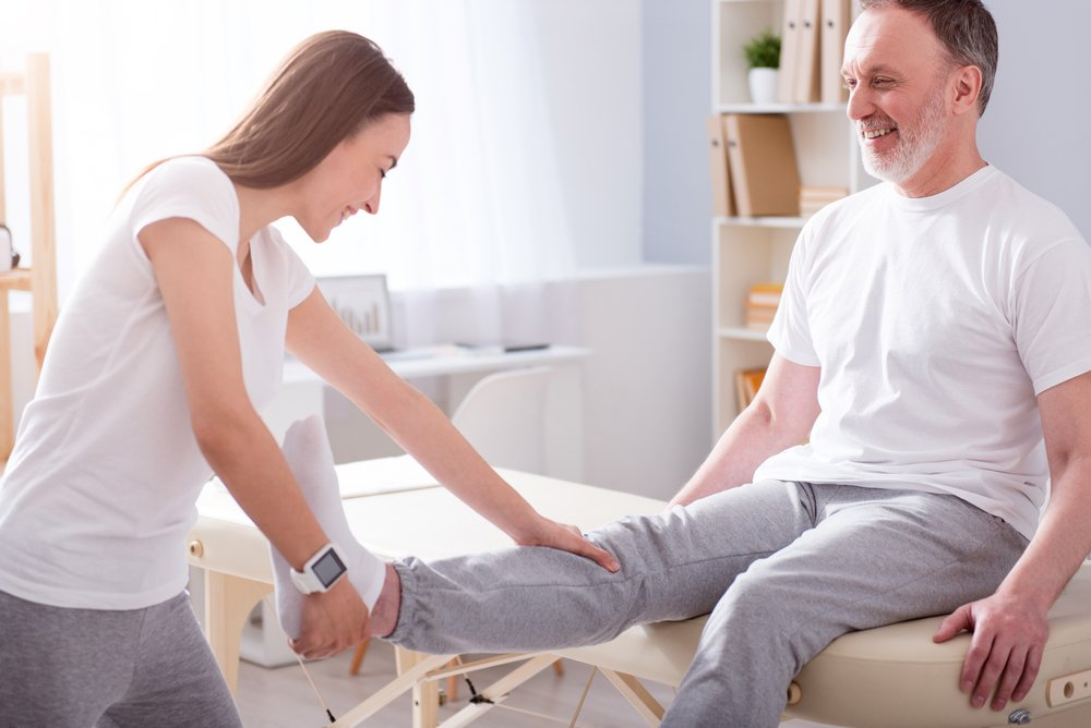 female physical therapist assisting a man for his physical therapy session