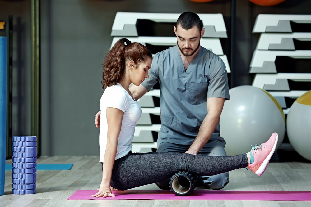 woman with a foam roller under her leg in a physical therapy session