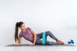woman going a clamshell exercise with a resistance band