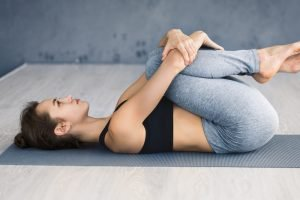 woman with her knees pushed to her chest to stretch