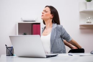 woman at her desk stretching by squeezing her shoulder blades with her arms behind her
